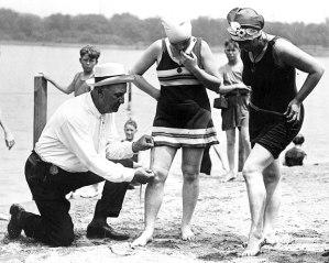 Policial mede o tamanho da roupa de banho de mulheres na praia, para garantir que sejam compatíveis a regulação da época em Palm Beach (1925)
